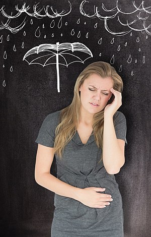 Eine Frau mit Kopf und Bauchschmerzen vor einer Wand mit Zeichnungen von Regen und Regenschirm.