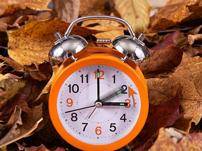 Altmodischer Wecker auf Herbstlaub.