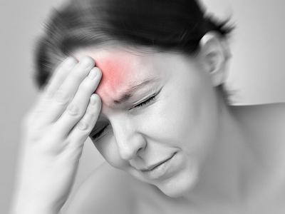 Eine Frau hat starke Kopfschmerzen.
