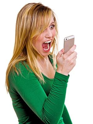 Frau im grünen Pullover schreit in ihr Telefon.