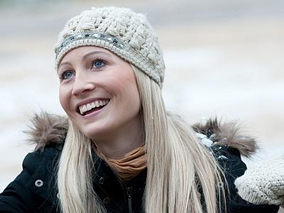 Eine lachende blonde Frau mit Mütze und Parka.