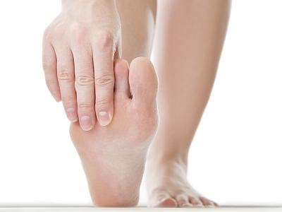 Eine Frau untersucht ihren Fuß