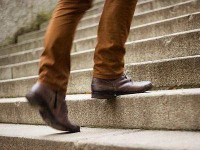 Nahaufnahme, Mann in Lederschuhen geht eine Außentreppe hinauf.