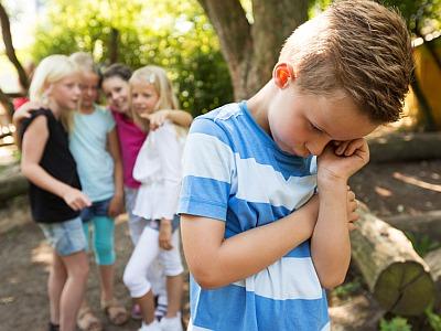 Kleiner Junge wird von einer Gruppe Mädchen gemoppt.