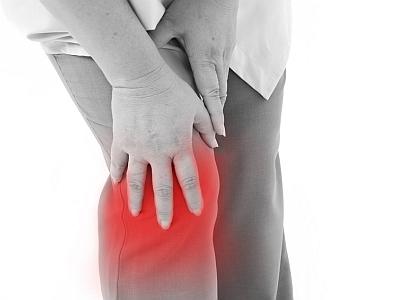 Eine Frau fasst sich an das schmerzende Knie.
