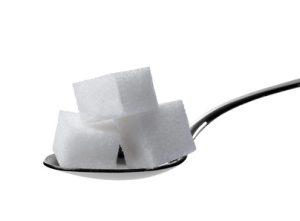 3 Zuckerwürfel auf einem Löffel