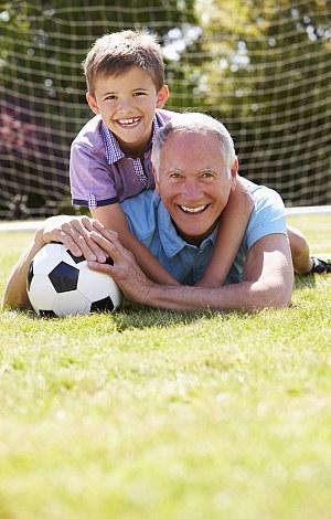 Opa und Enkel spielen fröhlich mit dem Fußball.