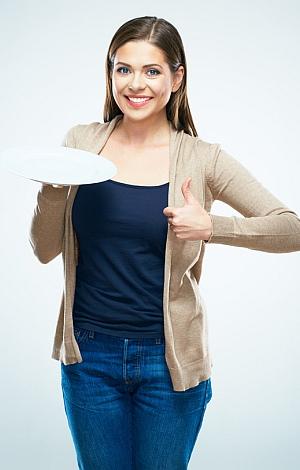 Junge Frau freut sich über Ihren leeren Teller und streckt den Daumen in die Höhe.
