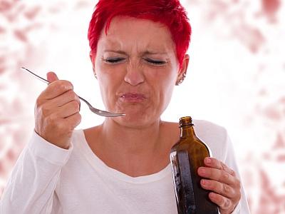 Frau nimmt Hustensaft, der eklig schmeckt und verzieht das Gesicht.