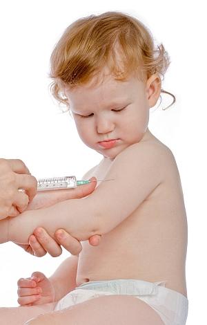 Ein kleines Kind schaut interessiert auf die Impfnadel.