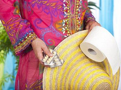Frau in Urlaubskleidung mit Tabletten, Hut und Toilettenpapierrolle in der Hand.