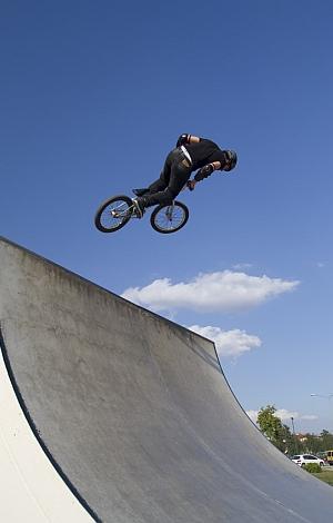 Ein Junge wagt mit dem Fahrrad einen Sprung auf einer Rampe.