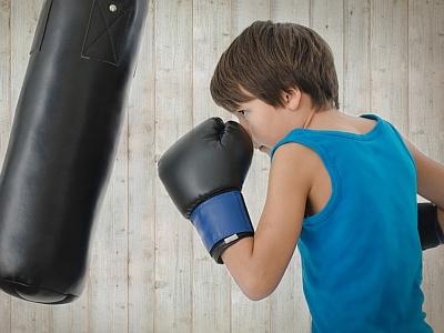 Junge im Sportdress boxt auf Boxsack.