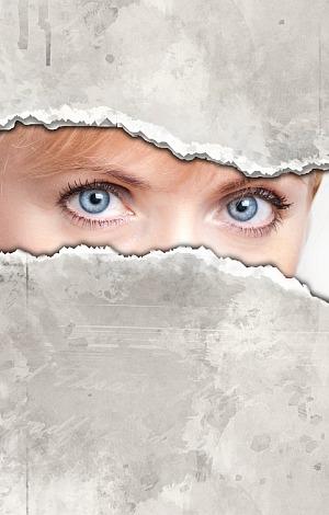 Blaue Augen sehen durch zerissenes Papier