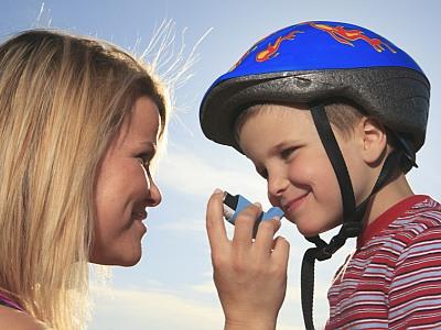 Eine Frau hilft einem Kind mit dem Asthmaspray.