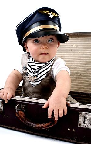 Ein Kind mit Pilotenkappe sitzt im Koffer.