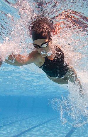 Unterwasseraufnahme einer Frau die im Schwimmbad krault.