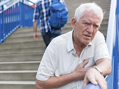Senior greift sich beim Treppensteigen ans Herz.