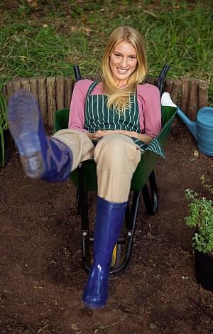 Junge Frau sitzt in einer Schubkarre und läßt die Beine baumeln.
