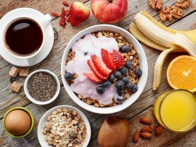 Frühstück mit Kaffee, Obst, Flocken, Ei und Saft