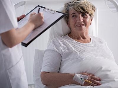 Frau im Krankenbett wird befragt.