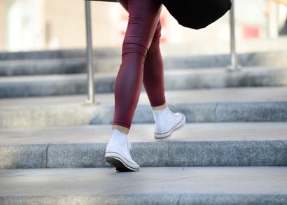 Frau mit Turnschuhen und roter Hose steigt Treppen