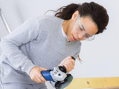 Junge Frau mit einer Schleifmaschine