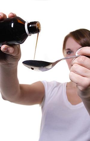 Frau gießt Hustensaft auf Löffel.