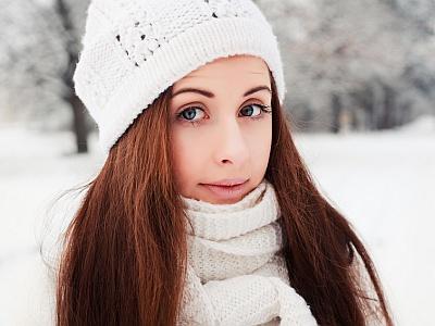 Junge Frau mit schönen Haaren und Mütze im Winter.