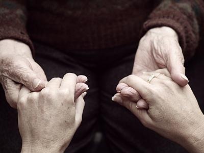 Alte und junge Hände halten sich fest.