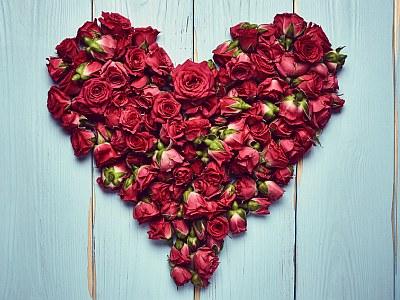 Herz aus roten Rosen auf Holzgrund.