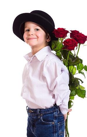 Kleiner Junge mit Hut und roten Rosen.