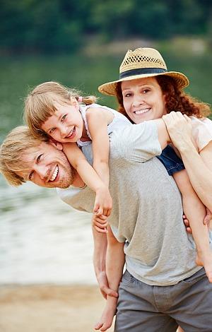 Glückliche Familie mit Tochter macht Urlaub im Sommer am See