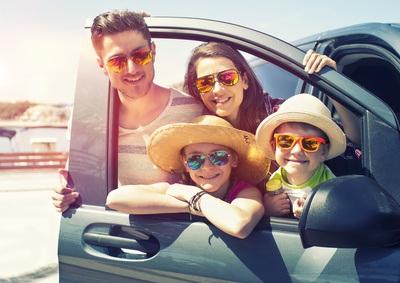 Familie im Auto mit Sonnenbrillen.