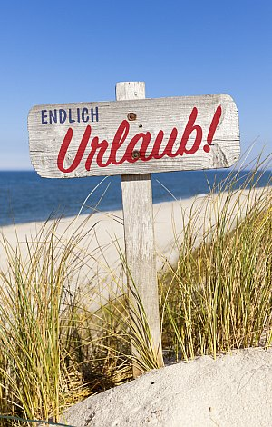 Endlich Urlaub - altes Holzschild in der Düne am Strand