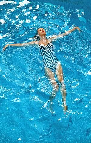 Frau liegt entspannt auf dem Rücken im Pool
