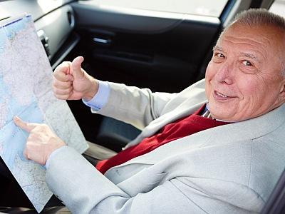 Älterer Mann mit Landkarte am Steuer.