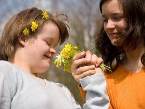 Ein behindertes Kind mit gesunder Schwester schnuppern an Blumen.