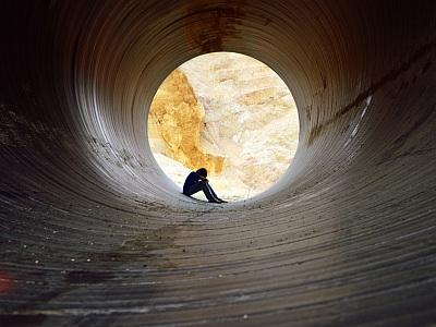 Mann sitzt depressiv im Tunnel.