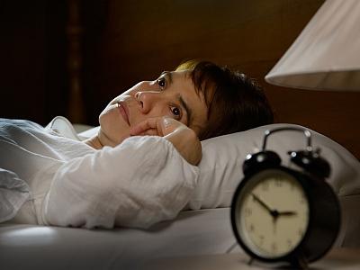 Frau liegt schlaflos im Bett.